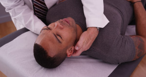 African-american male patient having neck pain examined by chiro